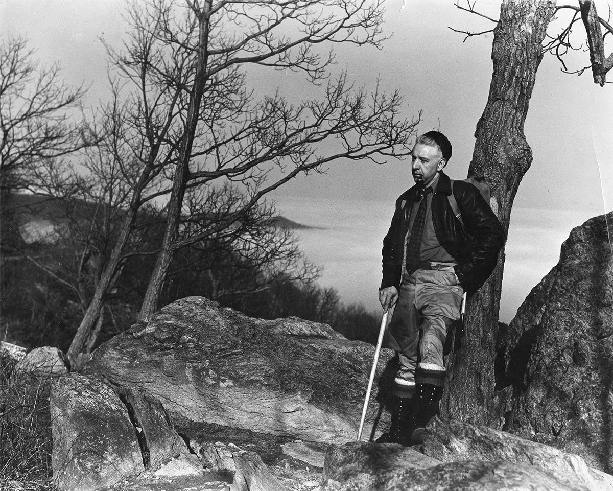 Early hiker with walking stick leans on blazoned tree (Courtesy of the Appalachian Trail Conservancy)